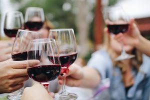 Menschen stoßen mit Rotwein an