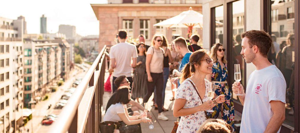 Lachende Menschen auf Terrasse mit Weinglas