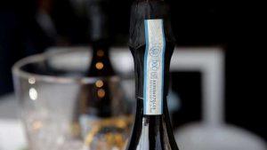 Prosecco DOC Steuerbanderole auf einem Flaschenhals, im Hintergrund eine weitere Flasche im Kühler.