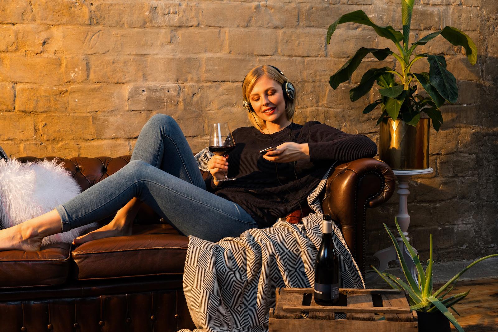 Junge Frau sitzt auf dem Sofa mit einem Glas Rotwein und einem Handy in der Hand.