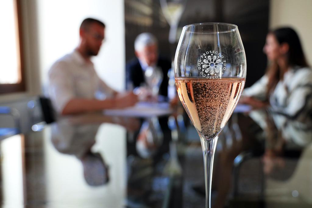 Ein Glas mit Prosecco DOC Rosé steht im Vordergrund auf dem Tisch.